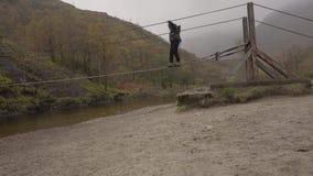 Kobieta zaczyna krzyżować drucianego most nad Nevis rzeką, Szkocja zbiory wideo