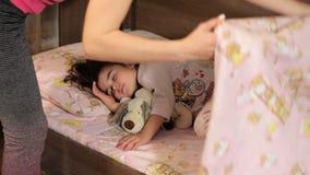Kobieta zakrywa sypialnej dziewczyny z koc i całuje ona Buziak dla nocy Dziewczyna śpi obejmujący miękką część zdjęcie wideo