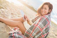 Kobieta zakrywająca z powszechnym używa pastylka pecetem przy plażą Obrazy Stock