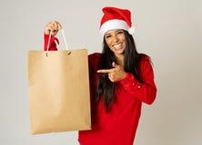 Kobieta zakupy dla boże narodzenie prezentów z torba na zakupy i Santa kapeluszowym patrzeć excited i szczęśliwy obrazy royalty free