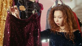 Kobieta zakupy dla nowej sukni w sklepie odzieżowym zbiory wideo