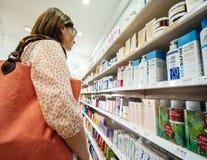 Kobieta zakupy dla różnorodnych piękno produktów w parapharmacy Zdjęcia Royalty Free