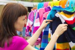 Kobieta zakupy odziewa na kramu przy bazarem zdjęcia stock