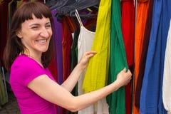 Kobieta zakupy odziewa na kramu przy bazarem Obrazy Stock