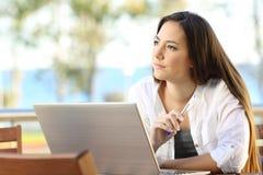 Kobieta zastanawia się pracować na plażowym mieszkaniu Fotografia Stock