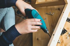 Kobieta zgromadzenie drewniany meble, naprawianie lub naprawianie dom z świderu narzędziem, nowożytni żywi pojęcia obraz royalty free