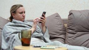 Kobieta zimno w domu Kłamać na leżance z telefonem zdjęcie wideo