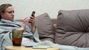 Kobieta zimno w domu Kłamać na leżance z telefonem zbiory wideo