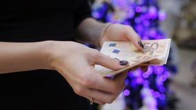 Kobieta znajduje pieniądze na tle girlandy choinka Czas kupować prezenty dla bożych narodzeń zbiory