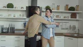 Kobieta znajduje za mężczyzny cyganieniu telefonem w kuchni zdjęcie wideo