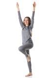 Kobieta zostaje na jeden nodze i rozciąga ręki up w szarych sportów termicznej bieliźnie Fotografia Stock