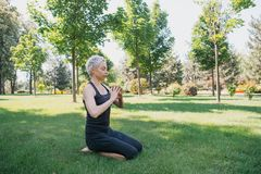 kobiety ćwiczy joga, robić gest z rękami na trawie i zdjęcia royalty free