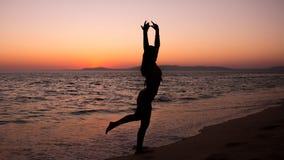 Kobiety ćwiczy joga, zmierzch w plaży Zdjęcie Royalty Free