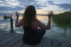 Kobiety ćwiczy medytacja w lotosowej joga pozycji na drewnianym jetty zdjęcie stock