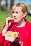 Kobiety łasowania hamburger i francuzów dłoniaki Zdjęcia Royalty Free