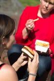 Kobiety łasowania hamburger i francuzów dłoniaki Fotografia Stock