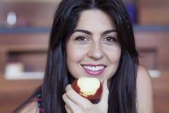 Kobiety łasowania jabłczana ono uśmiecha się szczęśliwa patrzeje kamera Obraz Stock