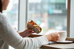 Kobiety łasowania kanapka i pić przy kawiarnią kawa Obraz Royalty Free
