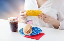 Kobiety łasowania kukurudza z hot dog i kolą obrazy royalty free