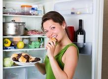 Kobiety łasowania tort od fridge Obrazy Royalty Free