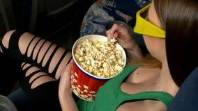 Kobiety łasowania wielki zbiornik popkorn w kinie zbiory wideo