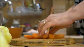 Kobiety żona w kuchennej tnącej świeżej marchewce przygotowywa jarzynowego naczynie zbiory