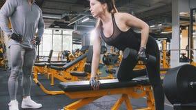 Kobiety atlety podnośni dumbbells w gym - powozowy obserwuje trenować Fotografia Royalty Free