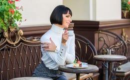 Kobiety atrakcyjna elegancka brunetka je smakosz kawiarni tarasu tortowego tło Przyjemny czas i relaks deliciouses obrazy royalty free