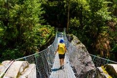 Kobiety backpacker krzyżuje zawieszonego most w Annapurna konserwaci terenie na trekking ścieżce, Nepal zdjęcia royalty free