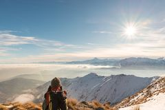 Kobiety backpacker odpoczywa na góra wierzchołku Tylni widok, zima styl życia, zimny uczucie, słońce gwiazda w backlight fotografia royalty free