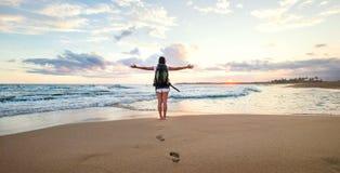 Kobiety backpacker powitanie zmierzch przy oceanu wybrzeżem Zdjęcia Royalty Free