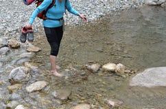 Kobiety backpacker przechodzi rzekę fotografia stock