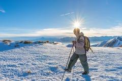 Kobiety backpacker trekking na śniegu na Alps Tylni widok, zima styl życia, zimny uczucie, słońce gwiazda w backlight zdjęcie royalty free