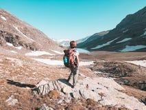 Kobiety Backpacker wycieczkuje w idyllicznym krajobrazie, siklawie i kwitnącej łące, Lato eksploracja na Alps i przygody stonowan zdjęcie royalty free