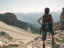 Kobiety Backpacker wycieczkuje w idyllicznym krajobrazie, siklawie i kwitnącej łące, Lato eksploracja na Alps i przygody stonowan zdjęcia stock