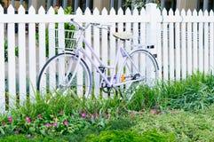 Kobiety bicycl chudy przy bielu ogrodzeniem Zdjęcia Stock
