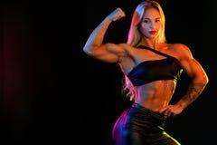 Kobiety bodybuilder mistrza atleta na czarnym tle, zdjęcie stock