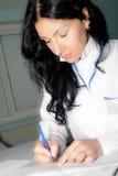 Kobiety brunetki lekarka pisze anamnezie Zdjęcia Royalty Free