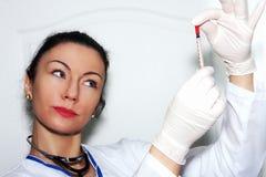 Kobiety brunetki lekarka sprawdza strzykawkę Obraz Royalty Free
