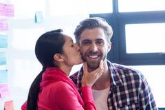 Kobiety całowania męski kolega w biurze Fotografia Royalty Free