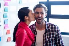 Kobiety całowania męski kolega w kreatywnie biurze Obraz Royalty Free
