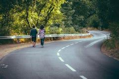 Kobiety chodzi na drogowym skrzyżowaniu pięknego lasu Obrazy Stock