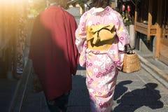 Kobiety chodzi przy świątynią z słońcem w tradycyjnych japońskich kimonach zdjęcia royalty free