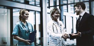Kobiety chwiania Doktorskie ręki z biznesmenem zdjęcia stock