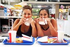 Kobiety cieszą się ich fast food Zdjęcia Royalty Free
