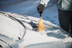 Kobiety cleaning śnieg od jej samochodu z miotłą zdjęcie royalty free