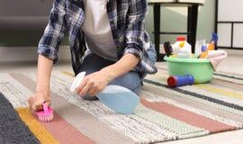Kobiety cleaning dywan z muśnięciem w domu, zbliżenie zdjęcia stock