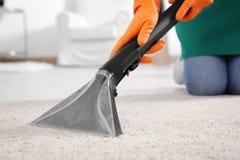 Kobiety cleaning dywan z próżnią obrazy stock