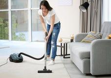 Kobiety cleaning dywan z próżnią w pokoju Obraz Stock