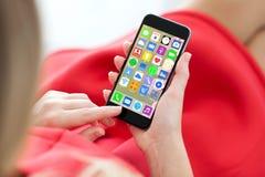Kobiety czerwieni sukni mienia telefon z domowego ekranu ikon apps Obrazy Royalty Free
